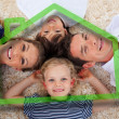 Smiling young family in front of green house illustration - Stock Photo