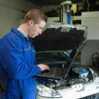 Male mechanic using laptop — Stock Photo
