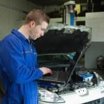 Male mechanic using laptop — Stock Photo