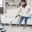 Woman wearing headphones while hoovering — Stock Photo