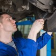 Auto mechanic repairing car with spanner - Stock Photo