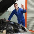 Mechanic by car making ok sign — Stock Photo