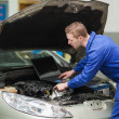 Auto mechanic with laptop repairing car — ストック写真