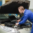 Auto mechanic with laptop repairing car — Stock Photo #24097713