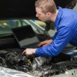 Repairman with laptop checking car engine — Photo