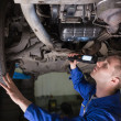 Foto Stock: Mechanic examining car