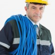 Mature man wearing hardhat with cable — Stock Photo #24098029