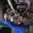 Auto mechanic working under car - Stock Photo