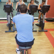 Stock Photo: Four women take spinning class