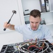 Frustrated mhitting cpu with hammer — Stock Photo #24098211