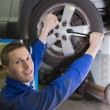 Male mechanic changing car tire — Stock Photo #24098315