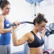 Woman using weights machine with female trainer — Stock Photo