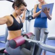 Female trainer taking notes on client on weights machine — Stock Photo