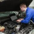 mechanik za pomocą laptopa na samochód silnik — Zdjęcie stockowe