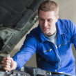 Mechanic working on automobile engine - Stock Photo