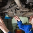 Auto mechanic working under car — Stock Photo #24098651