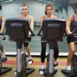 Stock Photo: Four women working out at spinning class