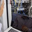 Stock Photo: Msitting with laptop in front of server