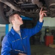 Auto mechanic with clipboard under car — Stock Photo #24098701