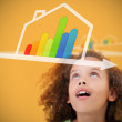 Stock Photo: Girl looking up to energy efficient house graphic