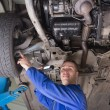 Auto mechanic examining car tire — Stock Photo #24098809