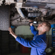 Male mechanic examining car — Stock Photo