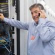 Stock Photo: Mfixing server wires and talking on phone