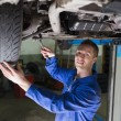 Stock Photo: Confident mechanic repairing car