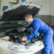 Stock Photo: Male mechanic analyzing car engine