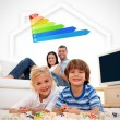 Two smiling children lying on a carpet with parents — Stock Photo