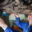 Portrait of mechanic working under car - Stock Photo