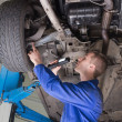 Auto mechanic examining under car — Stock Photo #24099471