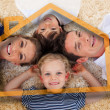 Smiling young family in front of orange house illustration - Stock Photo