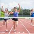 Athletes celebrating as they cross finish line — Stock Photo #24099513