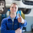 Stock Photo: Happy male mechanic gesturing thumbs up