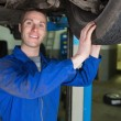 Happy mechanic examining car tire — Stok fotoğraf