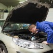 Mechanic working under car bonnet — Stock Photo #24099975