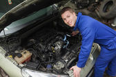 Happy mechanic examining car engine — Stock Photo