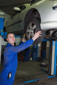 Car on hydraulic lift as mechanic examining tire — Stock Photo