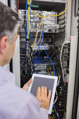Technician controlling the server with a digital tablet — Stock Photo