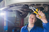 Happy mechanic repairing car with pliers — Stock Photo