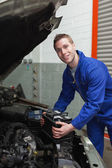 Happy mechanic with battery by car — Stock Photo