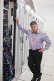 Man standing next to a server tower — Stock Photo