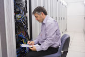 Technician writing notes on the servers — Stock Photo