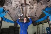 Mechanic inspecting under car — Stock Photo