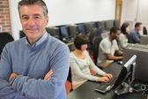 Teacher smiling at top of computer class — Stock Photo