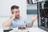Computer engineer on call as he gestures towards an open cpu — Stock Photo