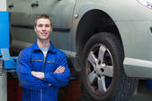 Confident male mechanic standing by car — Stock Photo