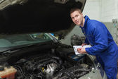 Mechanic with clipboard by car — Stock Photo