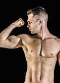 Shirtless young man flexing muscles — Stock Photo